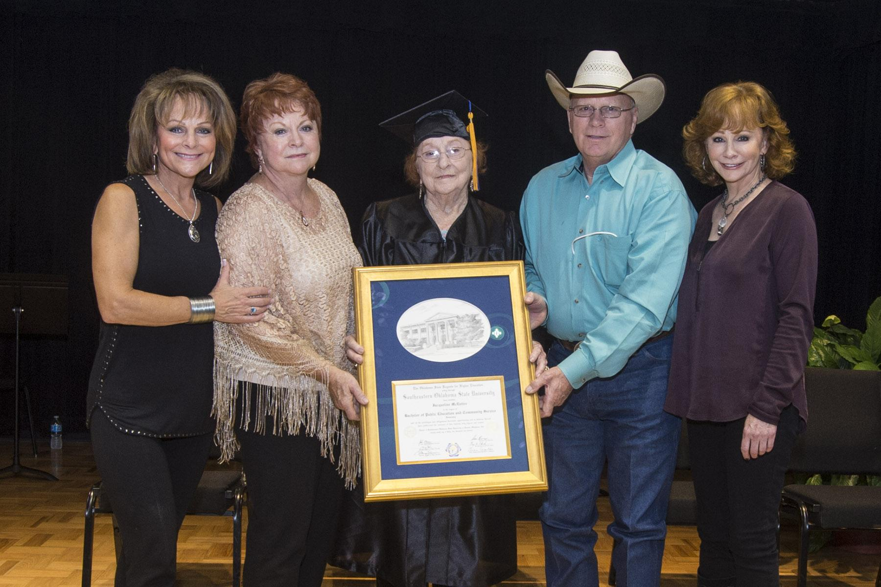 Mrs. Jacqueline McEntire, center, holds the honorary degree she received from Southeastern Thursday. Joining her are her children, Susie McEntire-Eaton, Alice Foran, Pake McEntire, and Reba McEntire.