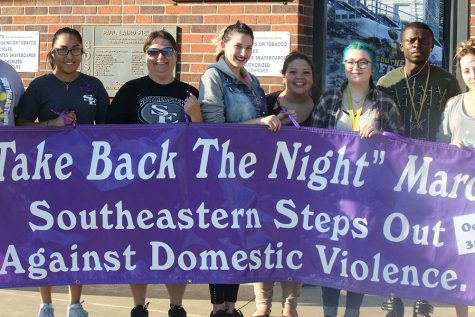 "Students hold Southeastern's ""Take Back the Night"" sign on October 3 in front of Paul Laird Field."