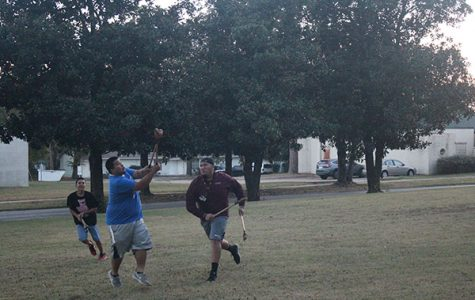 Members of NASA play stickball on the front lawn in honor of Native November.