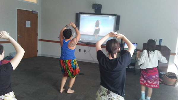 Gingerlei Waddell, Grounds Lands Supervisor, demonstrates Tahitian dance to a class of faculty, staff and students.