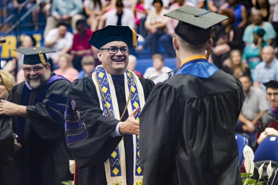 Southeastern president Sean Burrage congratulates a graduate Saturday at Bloomer Sullivan Arena.