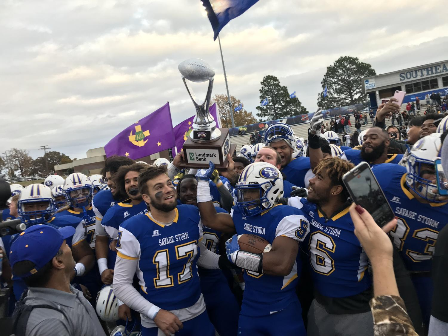 Southeastern players raise new trophy on the field after 27-24 win against ECU Tigers.