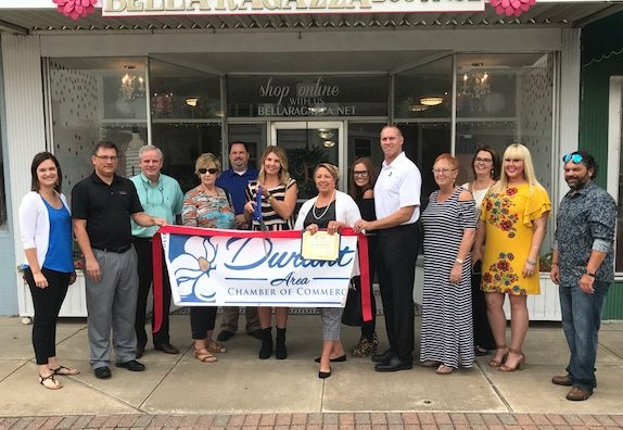 Bella Ragazza Boutique owner, Melissa Burrage, and Chamber of Commerce members meet in front of new location for ribbon cutting on September 12.