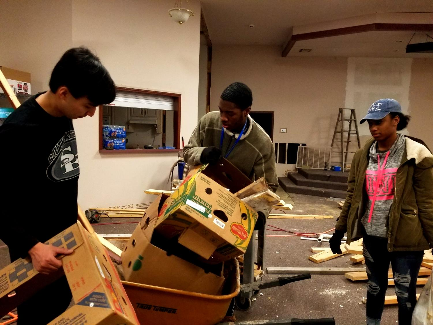 Dylan Candelora, Tay Pruitt and Jay Carr help remove trash from the J127 building on Jan. 21, 2019. Though volunteer activities may be different this year, their impact is not lessened.