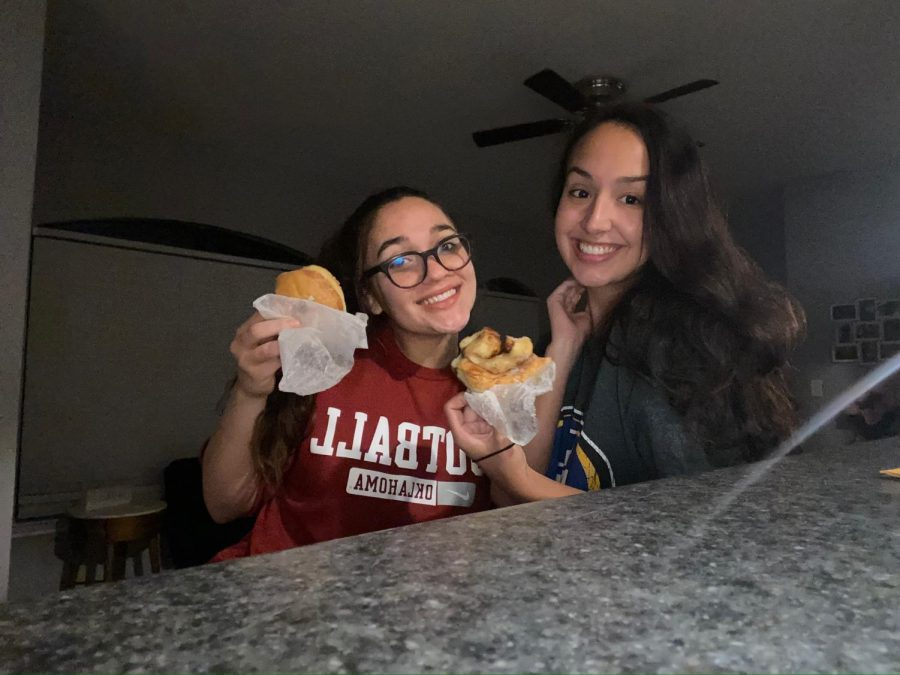 Mariah Fagan and Morgan Rosamond pose for a self-timer photo while enjoying their midnight snack of donuts from Dandy